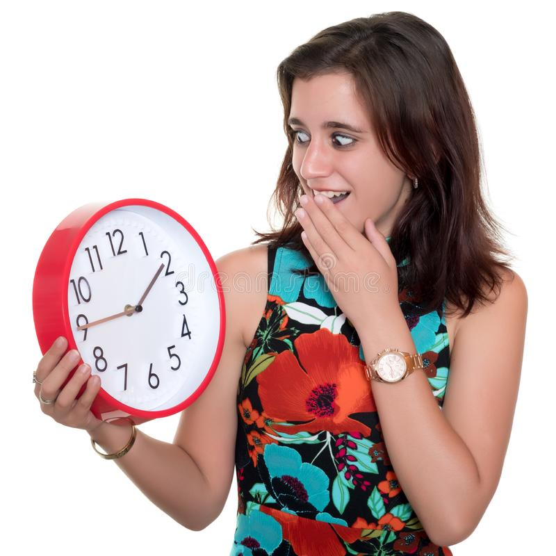 Teenage girl with a surprised expression checking the time on a big clock royalty free stock photos