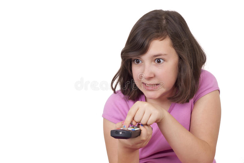 Beautiful teenage girl with tv remote control in her hands royalty free stock image