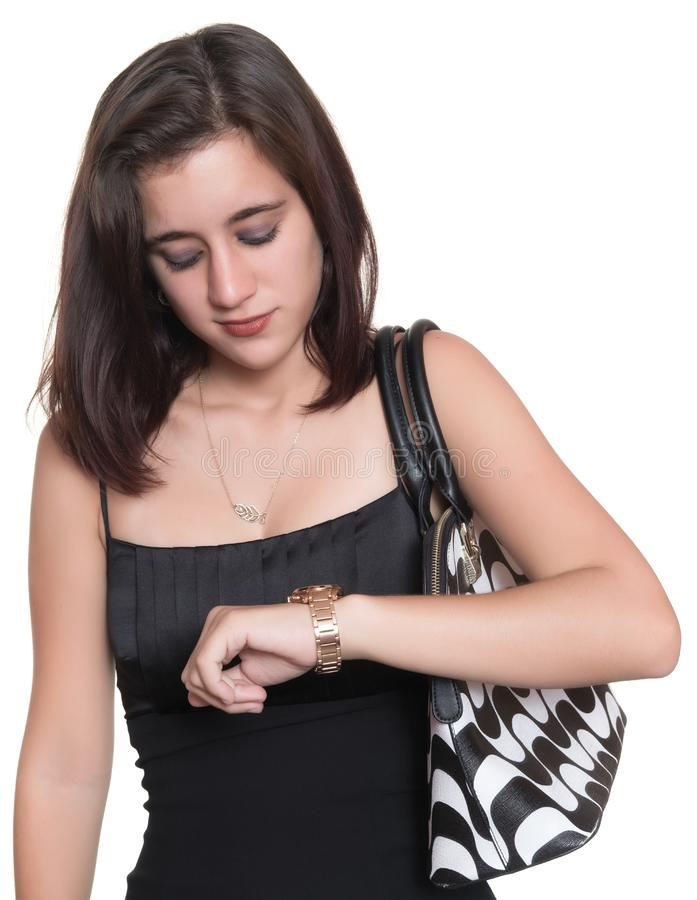Beautiful teenage girl wearing an elegant black dress checking the time on her watch stock photography