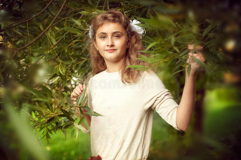 Beautiful teenage girl 10 years old with long blonde hair stands royalty free stock photos
