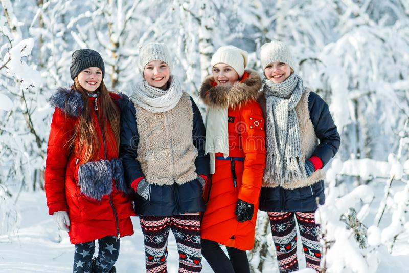 Beautiful teenage girls having fun outside in a wood with snow in winter. Friendship and active life consept royalty free stock image