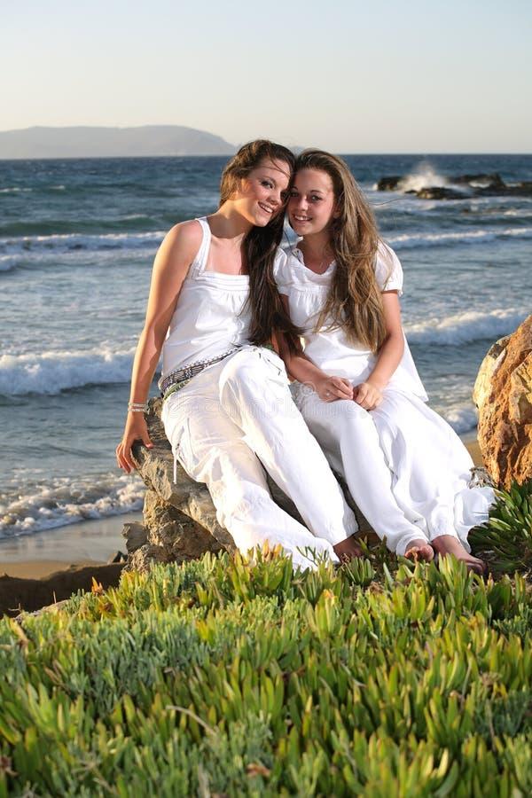 Beautiful teenage girls over sea and sunset backgr. Two beautiful teenage girls sitting over sea and sunset background royalty free stock image