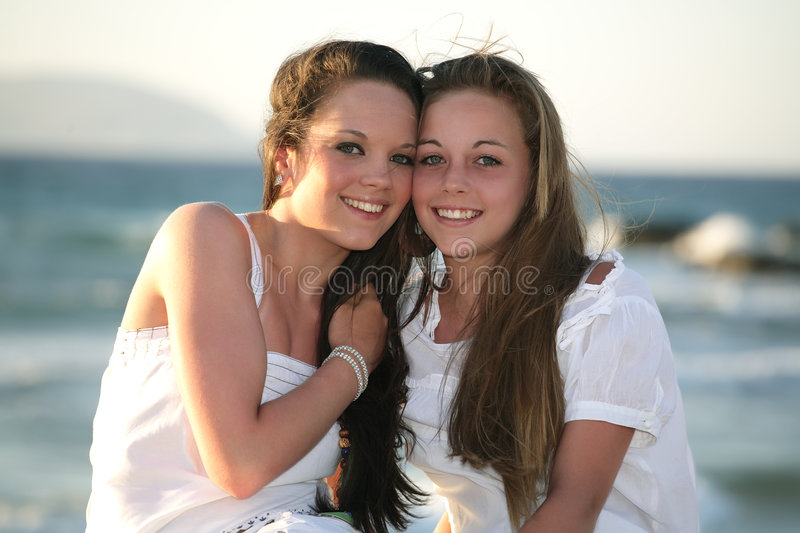 Beautiful teenage girls over sea and sunset backgr. Two beautiful teenage girls sitting over sea and sunset background royalty free stock photo