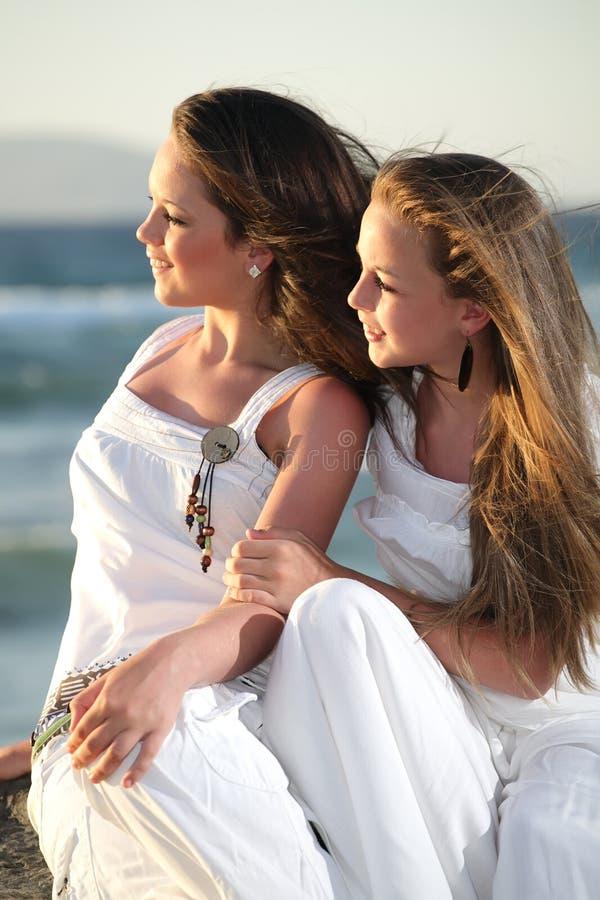 Beautiful teenage girls over sea and sunset backgr. Two beautiful teenage girls sitting over sea and sunset background stock photography