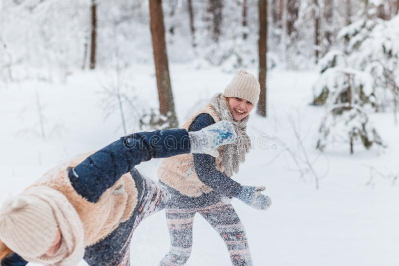 Beautiful teenage girls twins sisters having fun outside in a wood with snow in winter. Friendship, family, consept royalty free stock photography