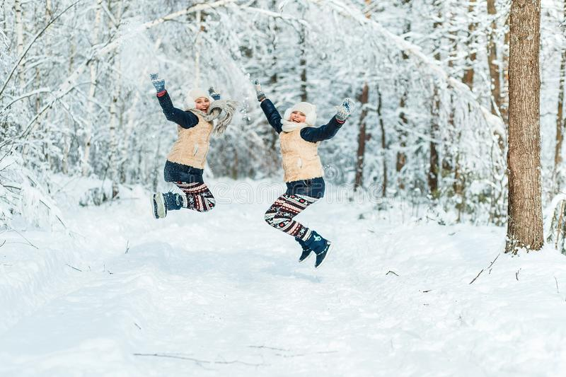 Beautiful teenage girls twins sisters having fun outside in a wood with snow in winter. Friendship, family, consept stock photo