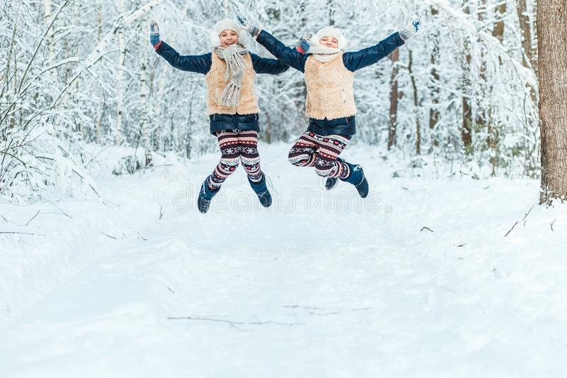 Beautiful teenage girls twins sisters having fun outside in a wood with snow in winter. Friendship, family, consept stock photos