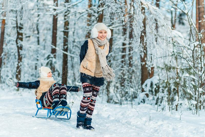 Beautiful teenage girls twins sisters riding sledge and having fun outside in a wood with snow . Friendship consept stock photography