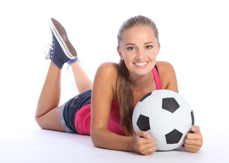Beautiful teenage soccer girl lying on floor stock photo
