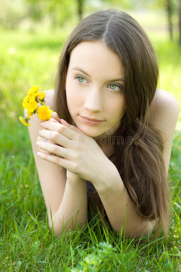 Beautiful teenager with dandelion on lawn. Young beautiful teenager with dandelion on lawn royalty free stock photo