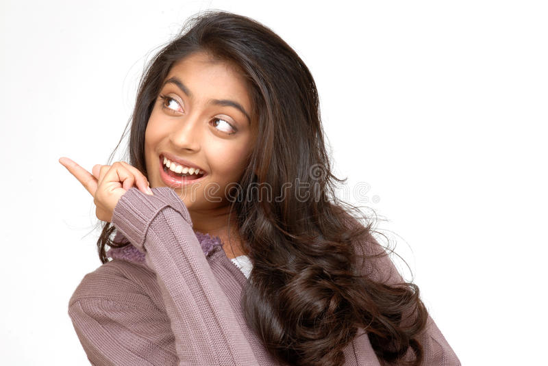 Beautiful teenager girl. Indian teenager girl pointing at copy-space stock image