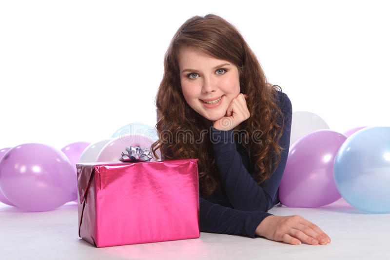 Beautiful teenager girl birthday party with gift. Beautiful teenager girl with bright blue eyes lying on the floor among party balloons with lovely happy smile stock photos