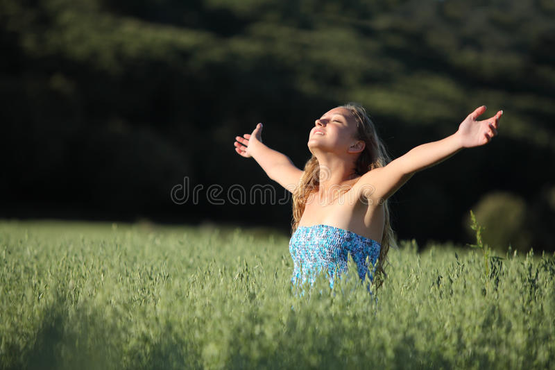 Beautiful teenager girl breathing happy in a green meadow stock image