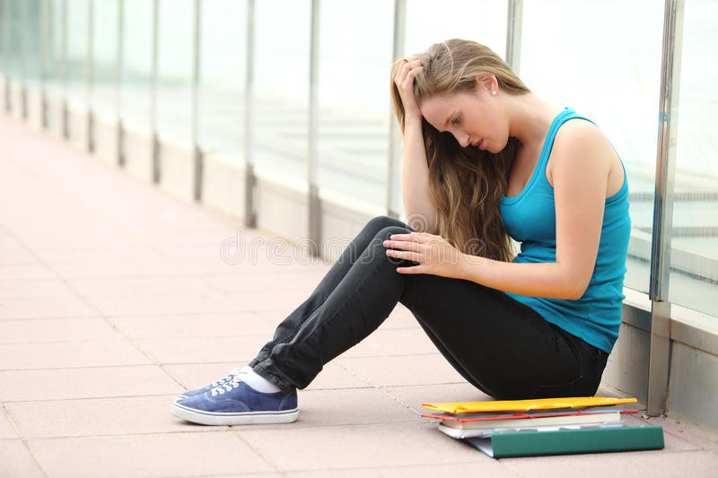 Beautiful teenager girl depressed sitting on the floor outdoor royalty free stock photo