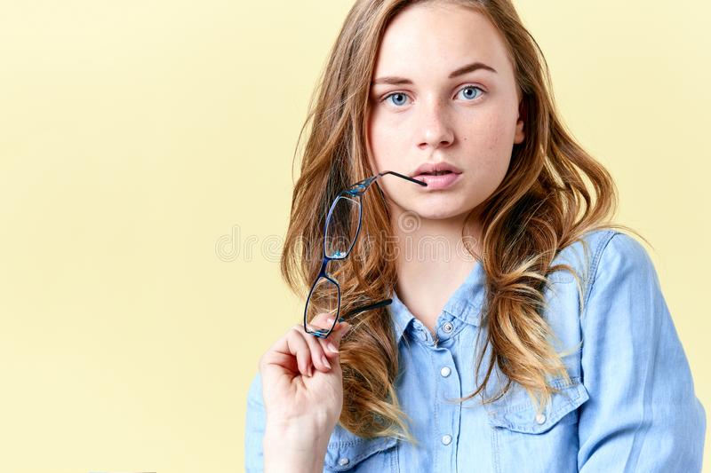 Beautiful teenager girl with ginger hair, freckles and blue eyes holding reading glasses, young woman with spectacles royalty free stock images