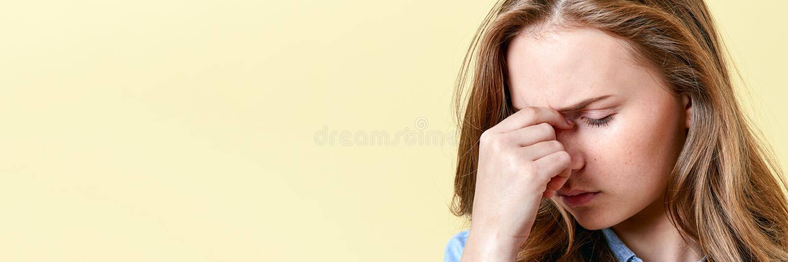 Beautiful teenager girl with ginger hair and freckles having headache and sore eyes. Tired student. stock image