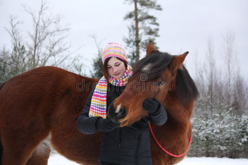 Beautiful teenager girl hugging brown horse in winter. Forest stock photos