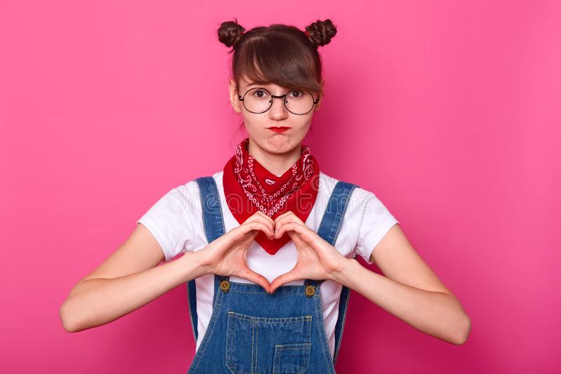 Beautiful teenager girl makes shape of heart with her hands on pink background. Gesture of love by pretty young student, looking. At camera with disappointed stock image