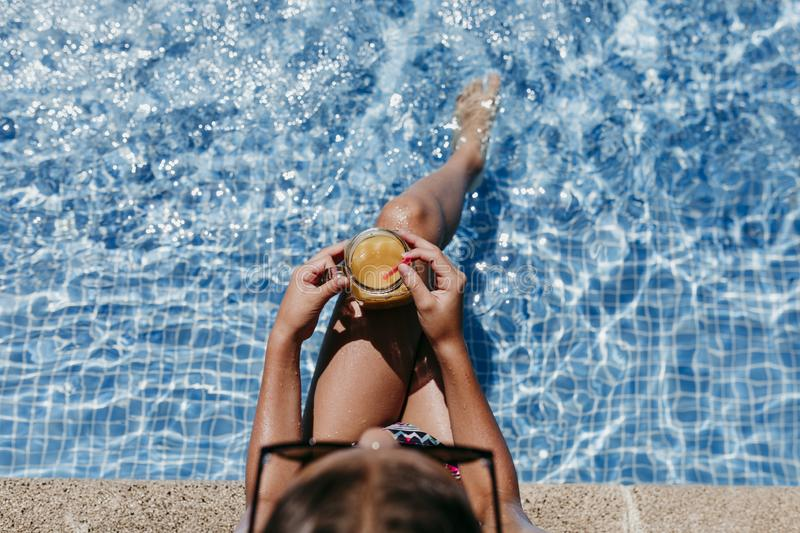 Beautiful teenager girl at the pool drinking healthy orange juice and having fun outdoors. Summertime and lifestyle concept. Top. View royalty free stock images