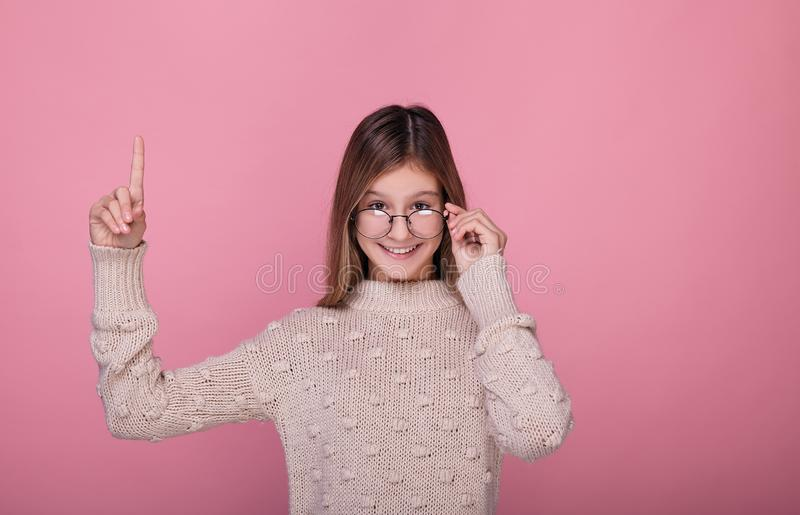 Beautiful teenager girl in round glasses shows a finger stock photos