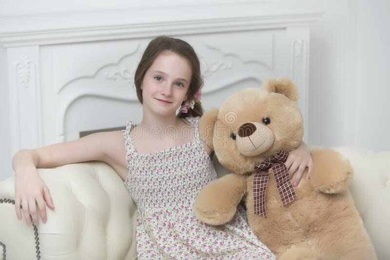 Beautiful teenager girl of school age sitting on the couch with. A teenage girl of school age is sitting on the couch with a big teddy bear. The concept of a stock photos