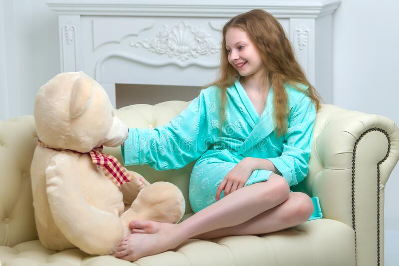 Beautiful teenager girl of school age sitting on the couch with. A teenage girl of school age is sitting on the couch with a big teddy bear. The concept of a stock photography