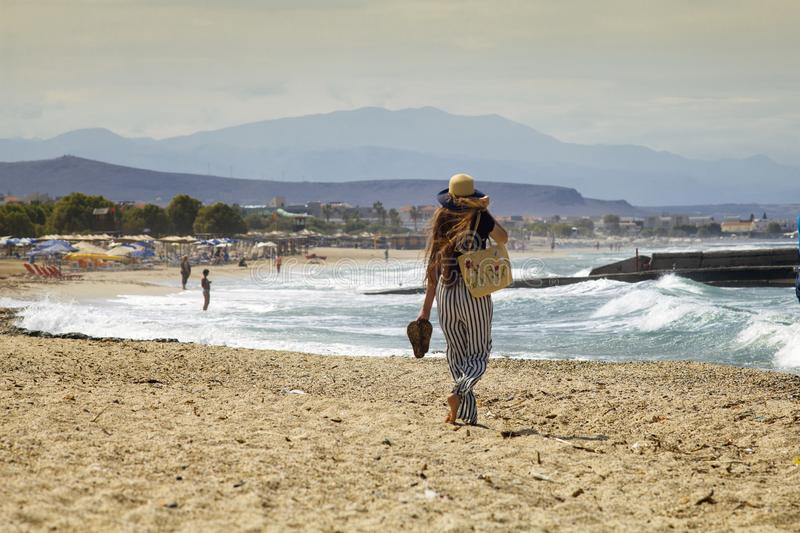 Beautiful teenager goes on the beach. The girl with her long hair is walking on the beach in Greece. stock photos