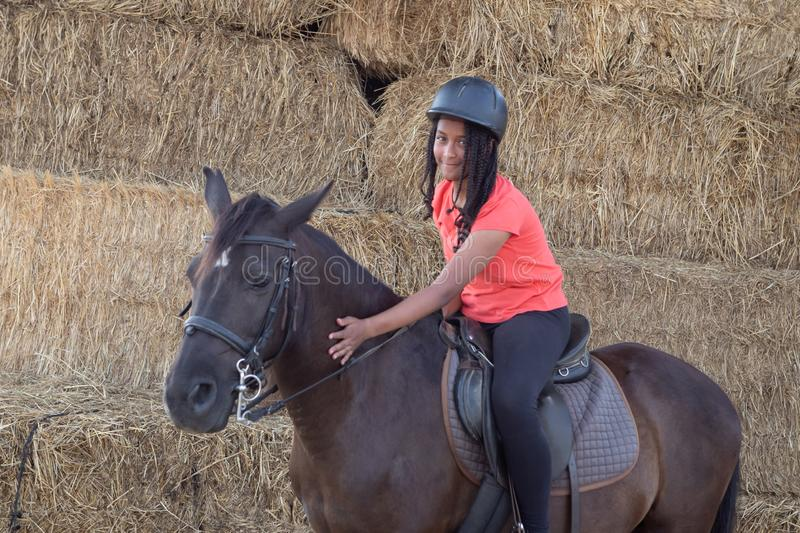 Beautiful teenager with his horse learning to ride royalty free stock photo