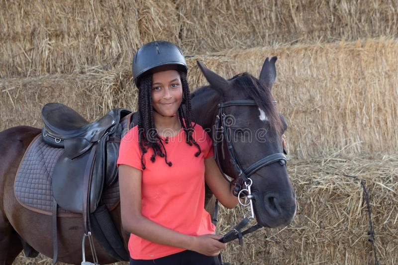 Beautiful teenager with his horse learning to ride royalty free stock images