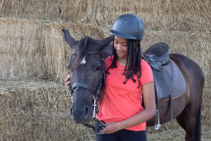 Beautiful teenager with his horse learning to ride stock photography