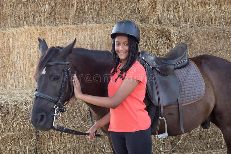 Beautiful teenager with his horse learning to ride royalty free stock photos
