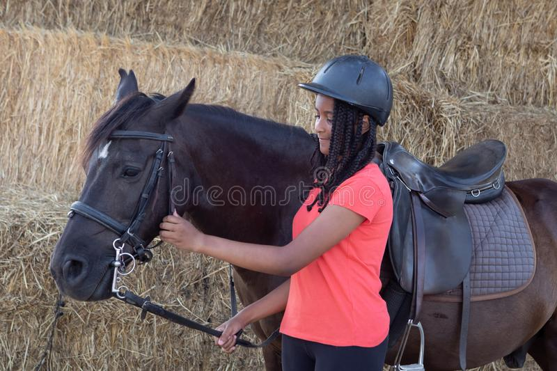 Beautiful teenager with his horse learning to ride royalty free stock image