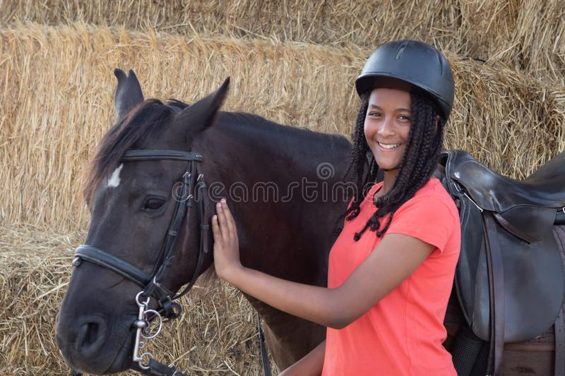 Beautiful teenager with his horse learning to ride stock photo