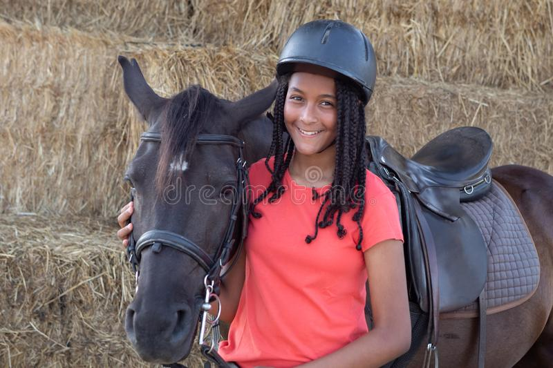 Beautiful teenager with his horse learning to ride stock images