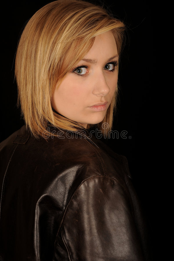 Beautiful teenager portrait. Half body portrait of beautiful blond teenager wearing leather jacket and looking over shoulder, black background stock image