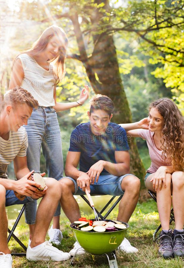 Teenagers camping, cooking vegetables on barbecue grill. Beautiful teenagers enjoying camping vacations in forest, cooking vegetables on barbecue grill stock photography