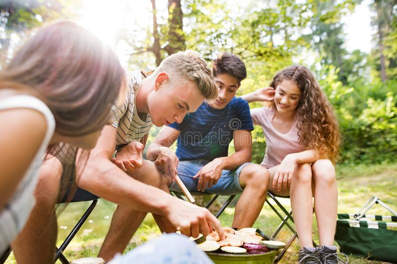 Teenagers camping, cooking vegetables on barbecue grill. royalty free stock photo