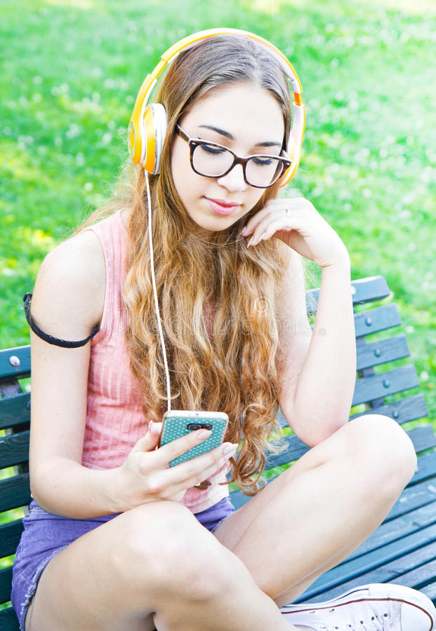 A beautiful teenger listen the music sit on the bench royalty free stock image