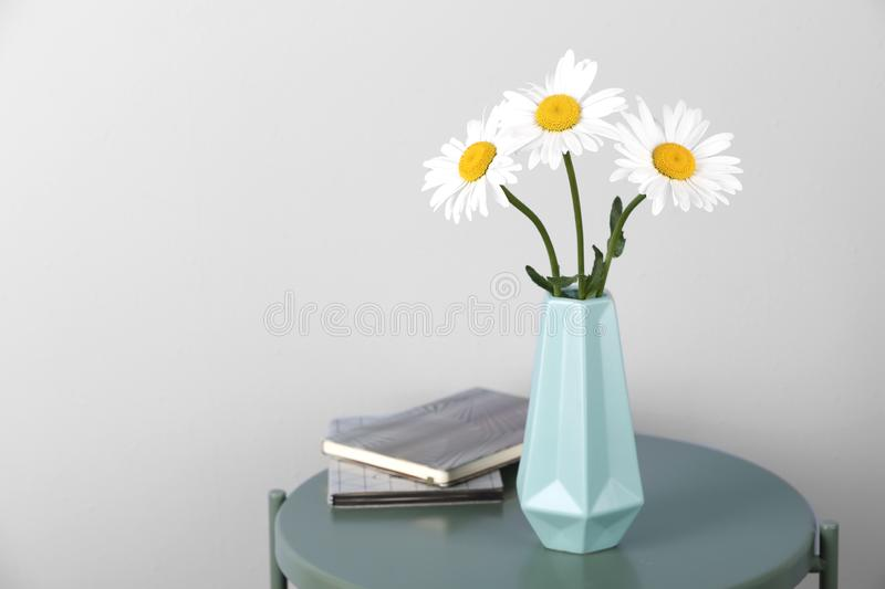 Beautiful tender chamomile flowers in vase and notebooks on table against light background royalty free stock photos