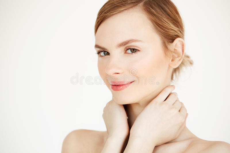 Beautiful tender girl with clean healthy skin smiling touching neck looking at camera over white background. Facial. Treatment. Copy space stock photography