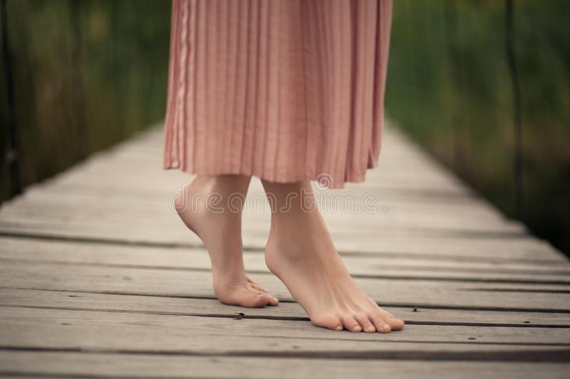 Beautiful tender girl in a peach-colored dress walking on a rural wooden bridge with a bouquet of flowers in hands royalty free stock image