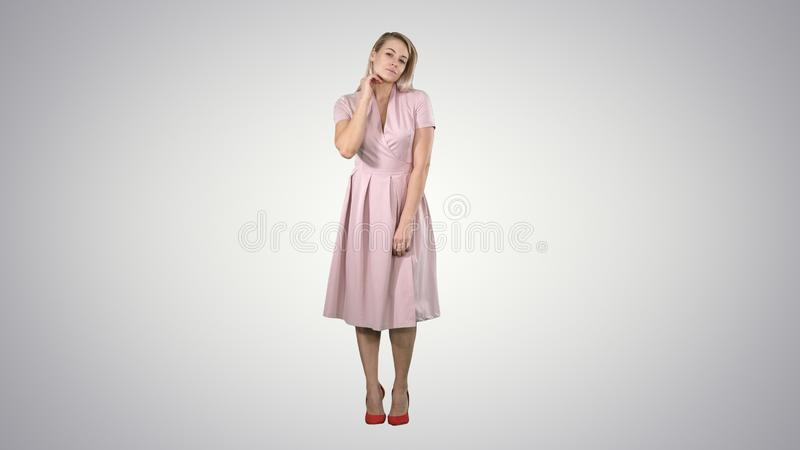 Beautiful tender girl in pink dress looking at the mirror on gradient background. Full length portrait. Beautiful tender girl in pink dress looking at the stock photo