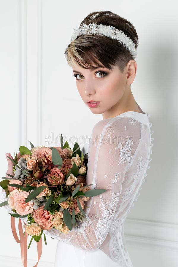 Beautiful tender bride girl with short haircut with crown on head with bouquet of flowers and elegant wedding dress royalty free stock photography