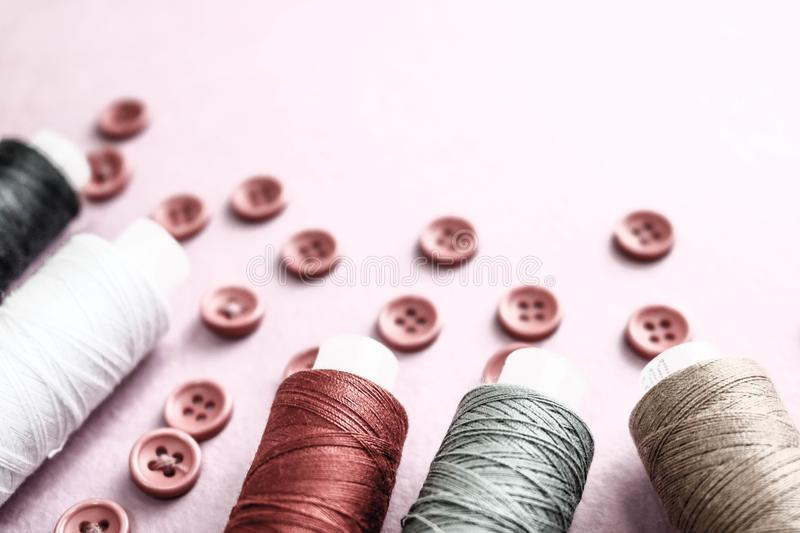 Beautiful texture with lots of round red buttons for sewing, needlework and skeins of spools of thread. Copy space. Flat lay. Pink, purple background royalty free stock photo