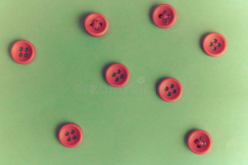 Beautiful texture with many round red buttons for sewing, needlework. Copy space. Flat lay. Green background stock photography