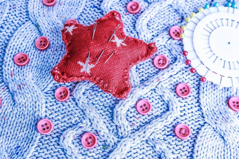 Soft warm natural sweater, fabrics with a knitted pattern of yarn and red small round buttons for sewing and a skein of red thread stock photography