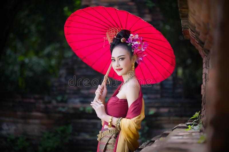 Beautiful Thai girl in traditional dress costume red umbrella as stock images
