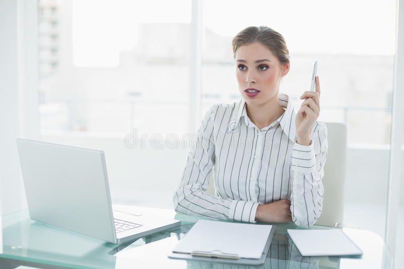 Beautiful thinking businesswoman holding a pen sitting at her desk royalty free stock photography