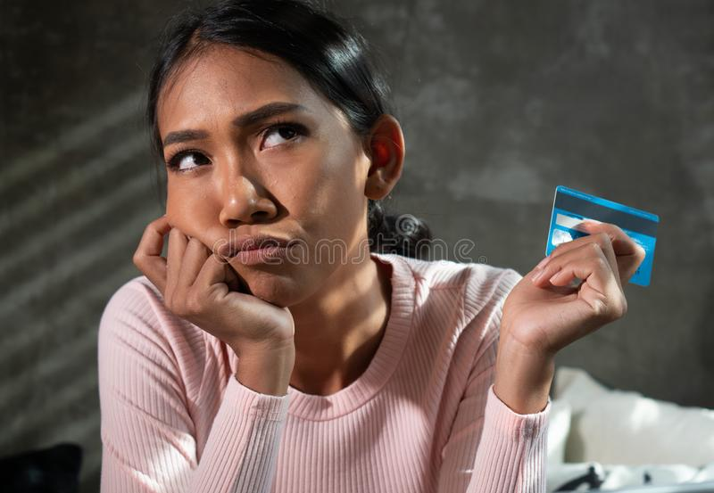 Beautiful thinking girl holding credit card while shopping online at home. Beautiful thinking girl holding banking card while shopping online at home. People stock image