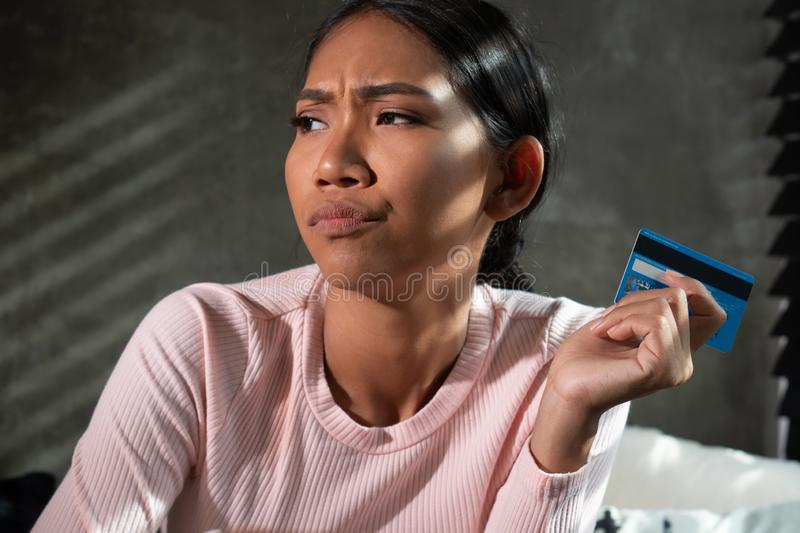 Beautiful thinking girl holding credit card while shopping online at home. Beautiful thinking girl holding banking card while shopping online at home. People stock photos